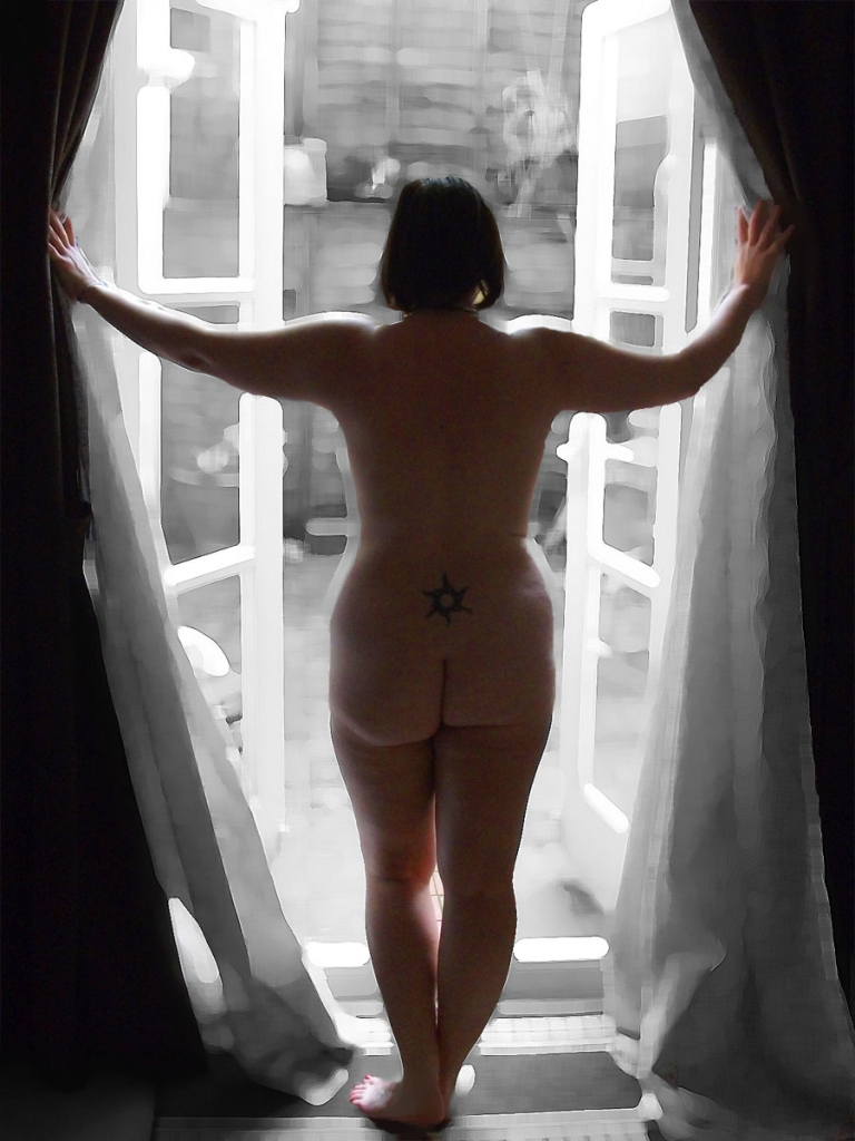 Woman standing naked in doorway looking out