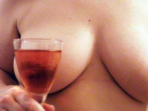 Glass of rosé wine in front of a woman's breast
