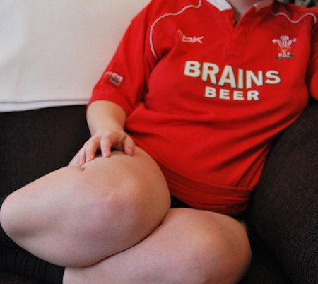 Woman in a Wales rugby shirt sitting of a sofa