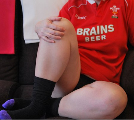 Woman in a Wales rugby shirt, sitting on sofa